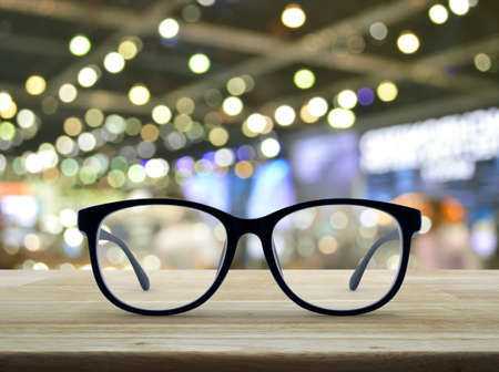 Black eye glasses on wooden table over blur light and shadow of shopping mall, Business vision concept Stock Photo