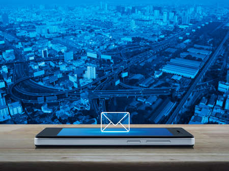 e commerce icon: email icon on modern smart phone screen on wooden table over city tower, street and expressway, Business communication concept