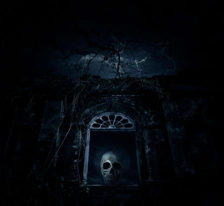 Crâne humain sur l'ancien château de la fenêtre avec un arbre mort sur la lune et le ciel nuageux, fond Spooky, concept d'Halloween