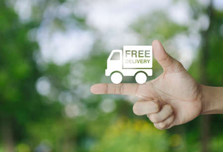 Free delivery truck icon on finger over blur green tree background, Transportation business concept