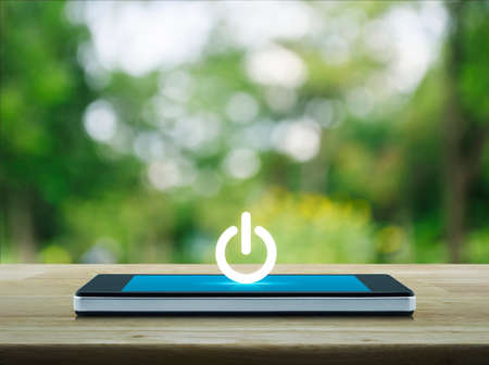 Power button icon on modern smart phone screen on wooden table over blur green tree in park, Start up business concept Foto de archivo