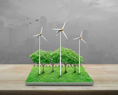 Wind turbines, trees, grass and birds from an open book on wooden table over blur pink flower and garden, Ecological concept