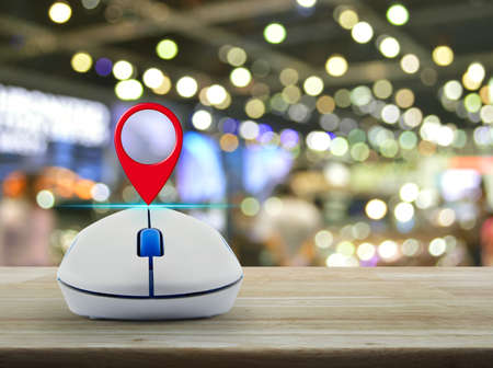 Map pin location button with wireless computer mouse on wooden table over blur light and shadow of shopping mall, Shopping navigation concept Stock Photo