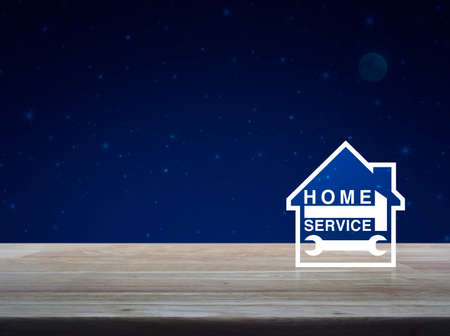 llave de sol: Martillo y llave con el icono de la casa en la mesa de madera sobre el cielo nocturno y la luna de fantasía, concepto de servicio de hogar de negocios