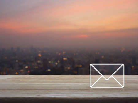 Mail icon on wooden table over blur of cityscape on warm light sundown, Contact us concept