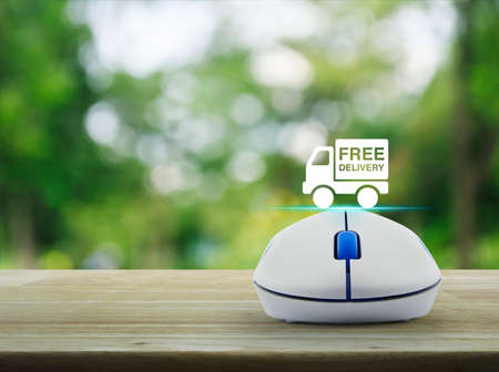 Free delivery truck icon with wireless computer mouse on wooden table over blur green tree in park, Business transportation concept