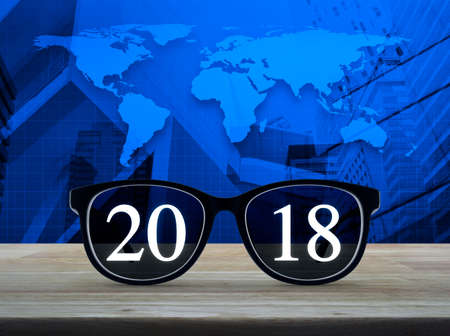 Retro flip clock with 2018 text on wooden table over aerial view 2018 white text with black eye glasses on wooden table over world map and city tower gumiabroncs Choice Image