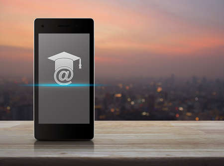 E-learning icon on modern smart phone screen on wooden table over blur of cityscape on warm light sundown, Study online concept