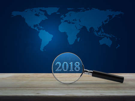 Magnifying glass with 2018 text and graph on wooden table over digital dot world map, Business happy new year concept