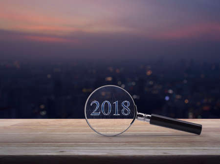 Magnifying glass with 2018 text and graph on wooden table over blur aerial view of city tower on warm light sundown, Business happy new year concept