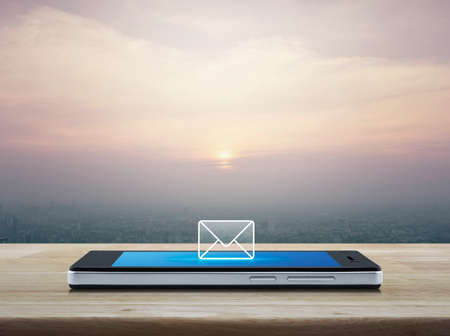 email icon on modern smart phone screen on wooden table over city tower at sunset, vintage style, Business communication concept Banque d'images