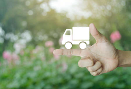 Truck delivery icon on finger over blur pink flower and tree, Transportation business concept Stock Photo