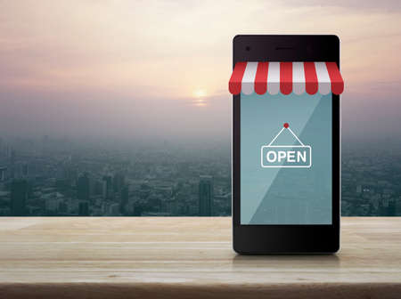 Modern smart mobile phone with on line shopping store graphic and open sign on wooden table over city tower at sunset, vintage style, Shop online concept Stock Photo