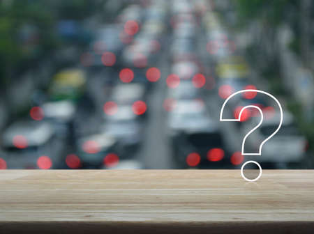 Question mark sign icon over blur of rush hour with cars and road, Customer support concept Stock Photo