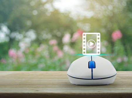 Play button and movie icon with wireless computer mouse on wooden table over blur pink flower and tree, Cinema online concept