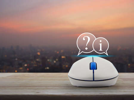 Question mark and information chat icon with wireless computer mouse on wooden table over blur of cityscape on warm light sundown, Customer support concept Stock Photo