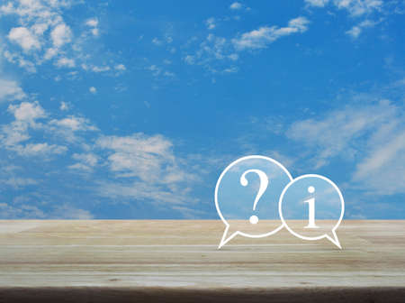 Question mark and information chat icon on wooden table over blue sky with white clouds, Customer support concept Stock Photo