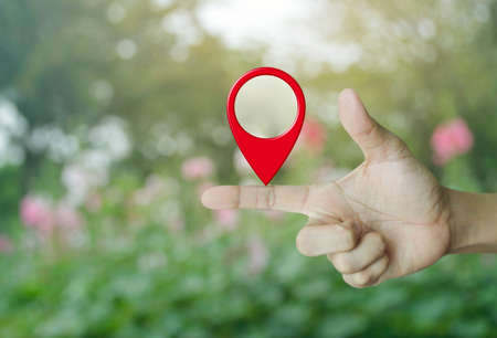 Map pin location button on finger over blur pink flower and tree, Map pointer navigation concept