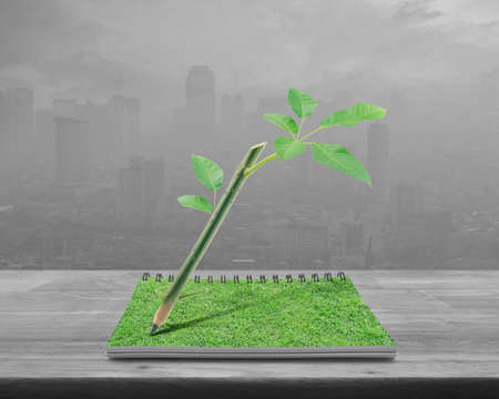 Wooden pencil with trunk tree and leaves on an open book on wooden table over pollution city tower, Green ecology idea concept Фото со стока
