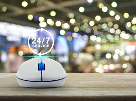 24 hours service icon with wireless computer mouse on wooden table over blur light and shadow of shopping mall, Full time service concept