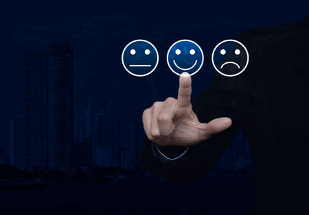 Businessman pressing excellent smiley face rating icon over world map and modern city tower, Business customer service evaluation and feedback rating concept