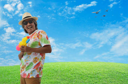 Happy elderly traveler asian man wearing summer t-shirt, straw hat and sunglasses holding colorful water gun over green grass with blue sky, clouds and birds, Summer water festival holiday concept Stock Photo