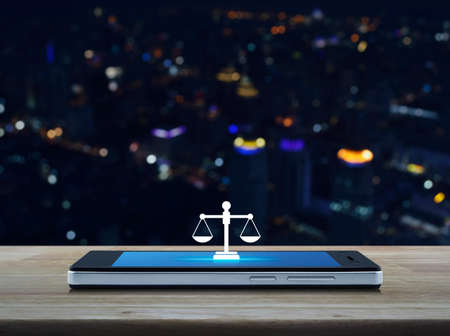 Law flat icon on modern smart mobile phone screen on wooden table over blur colorful night light city tower and skyscraper, Business legal service online concept