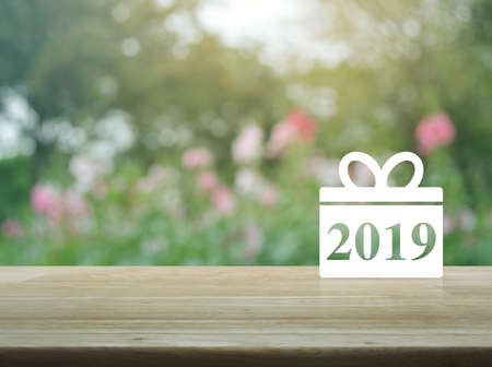 Gift box happy new year 2019 icon on wooden table over blur pink flower and tree, Business shop online concept Stock Photo