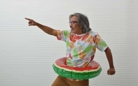 Happy funny elderly traveler asian man wearing summer t-shirt and eyeglasses in watermelon inflatable ring and pointing finger away over white wall, Business summer holiday concept