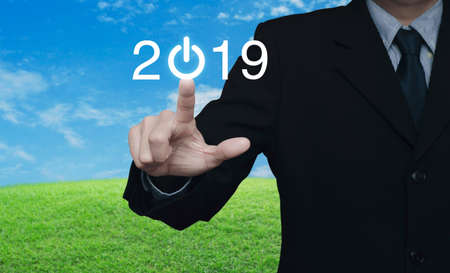 Businessman pressing 2019 start up business icon over green grass field with blue sky, Happy new year 2019 concept Stockfoto