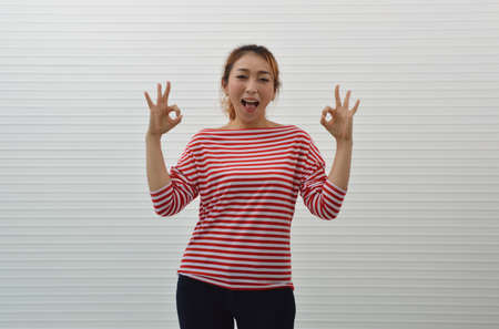 Cheerful young asian woman wearing red and white stripped shirt and jeans showing ok gesture sign with fingers over white wall background, Smiling facial expression Banco de Imagens
