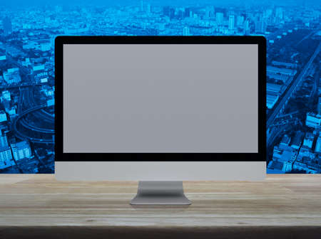 Desktop modern computer monitor with grey wide screen on wooden table over city tower, street, expressway and skyscraper