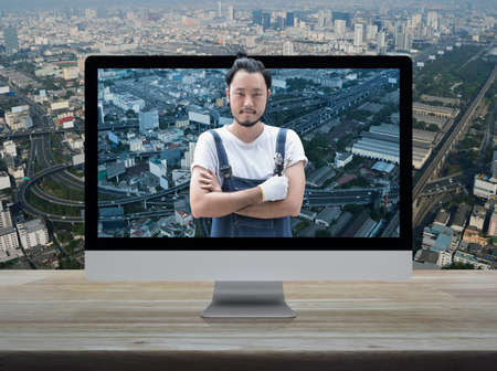 Asian mechanic car engine in uniform with tools on desktop modern computer monitor screen on wooden table over city tower, street, expressway and skyscraper, Business repair car online service concept Reklamní fotografie