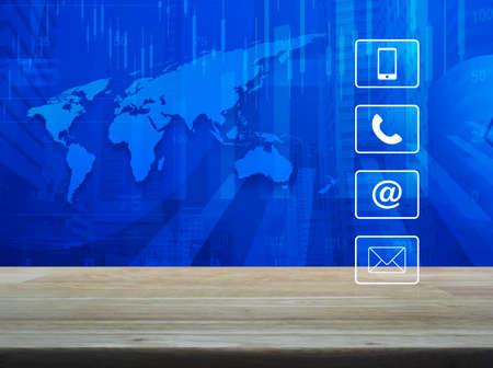 Telephone, mobile phone, www and email buttons on wooden table over world map with financial graph and modern city tower, Business customer support concept 스톡 콘텐츠