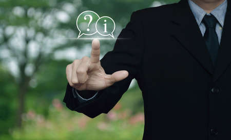 Businessman pressing question mark and information chat icon over blur flower and tree in park, Business customer service and support concept