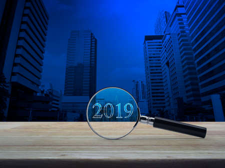 Magnifying glass with 2019 text and graph on wooden table over number and modern office city tower, Business happy new year research concept