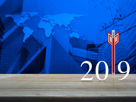 Red pencil in the shape of a dart with 2019 white text on wooden table over world map and city tower, Business strategy happy new year 2019 concept