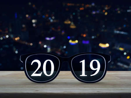 2019 white text with black eye glasses on wooden table over blur colorful night light of modern city tower and skyscraper, Business vision happy new year 2019 concept