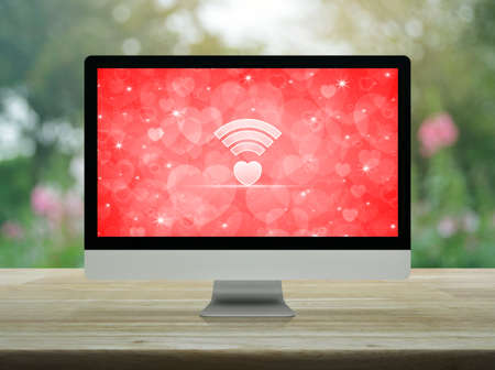 Heart love wifi flat icon on desktop modern computer monitor with red screen on wooden table over blur flower and tree in park, Internet online love connection, Valentines day concept