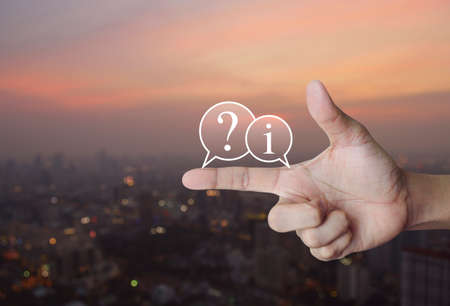 Question mark and information chat icon on finger over blur of cityscape on warm light sundown, Business customer support concept