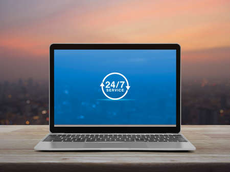 24 hours service icon with modern laptop computer on wooden table over blur of cityscape on warm light sundown, Business full time service online concept
