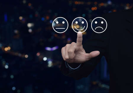 Businessman pressing excellent smiley face rating icon over blur colorful night light city tower, Business customer service evaluation and feedback rating concept
