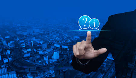 Businessman pressing question mark and information chat icon over modern city tower, street, expressway and skyscraper, Customer support concept