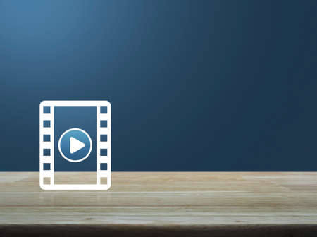 Play button with movie flat icon on wooden table over light blue gradient background, Business cinema online concept
