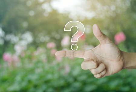 Question mark sign icon on finger over blur pink flower and tree in park, Business customer service and support concept