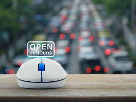 Open 24 hours icon with wireless computer mouse on wooden table over blur of rush hour with cars and road in city, Business full time service online concept