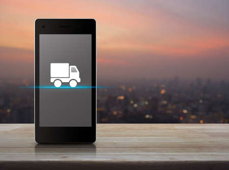 Truck delivery flat icon on modern smart mobile phone screen on wooden table over blur of cityscape on warm light sundown, Business transportation online concept