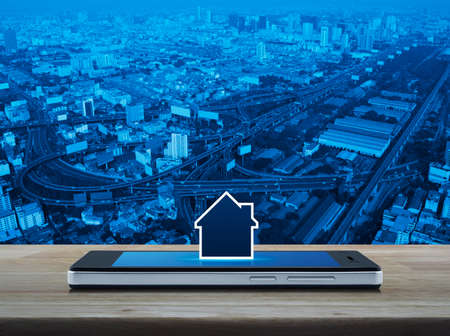 House icon with copy space on modern smart mobile phone screen on wooden table over city tower, street, expressway and skyscraper, Businesss real estate online concept