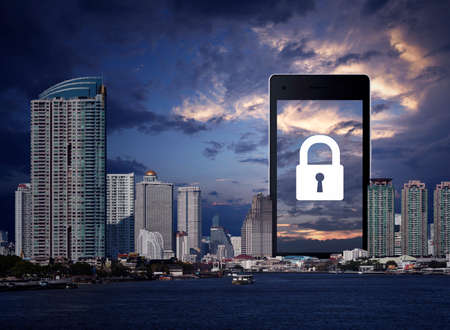 Key flat icon on modern smart mobile phone screen over office city tower, river, skyscraper and sunset sky, Business security online concept