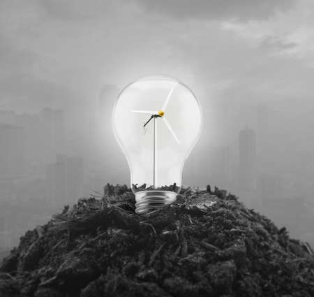 Light bulb with wind turbine inside on pile of soil over pollution city tower, Ecological power and energy concept Reklamní fotografie